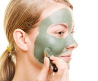 Woman applying with brush clay mud mask her face Stock Images