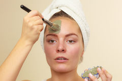 Woman applying with brush clay mud mask to her face Royalty Free Stock Photography