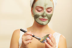 Woman applying with brush clay mud mask to her face. Skin care. Woman applying with brush clay mud mask to her face. Girl taking care of oily complexion. Beauty Stock Photos