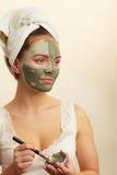 Woman applying with brush clay mud mask to her face Royalty Free Stock Photo