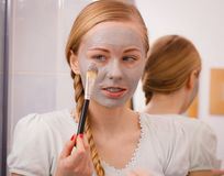 Woman applying with brush clay mud mask to her face Stock Photos