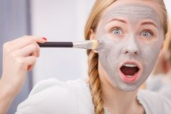 Woman applying with brush clay mud mask to her face. Skincare. Young funny woman applying with brush grey clay mud mask to her face. Female taking care of skin Stock Image