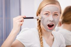 Woman applying with brush clay mud mask to her face. Skincare. Young funny woman applying with brush grey clay mud mask to her face. Female taking care of skin Stock Photo