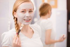 Woman applying with brush clay mud mask to her face. Skincare. Young woman applying with brush grey clay mud mask to her face. Female taking care of skin Stock Images