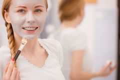 Woman applying with brush clay mud mask to her face. Skincare. Young woman applying with brush grey clay mud mask to her face. Female taking care of skin Royalty Free Stock Images