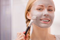 Woman applying with brush clay mud mask to her face Stock Images