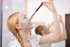 Woman applying with brush clay mud mask to her face. Skincare. Young playful woman applying with brush grey clay mud mask to her face. Female taking care of skin Stock Images