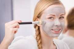 Woman applying with brush clay mud mask to her face Royalty Free Stock Photos