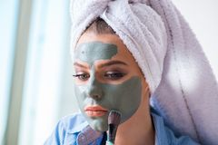 The woman applying clay mask with brush at home Stock Photography