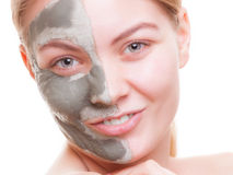 Woman applying clay mask on face. Spa. Royalty Free Stock Image