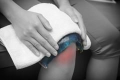 A woman applying cold pack on  swollen hurting knee Royalty Free Stock Image