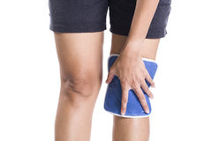 Woman applying cold pack on swollen hurting knee Royalty Free Stock Images