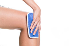Woman applying cold pack on swollen hurting knee Royalty Free Stock Photo