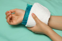 A woman applying cold pack on  swollen hurting wrist Royalty Free Stock Image