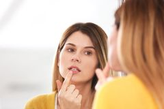 Woman applying cold sore cream on lips in front. Of mirror stock photos