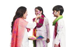 Woman applying color on the face of her daughter on Holi Stock Image