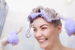 Woman applying toner shampoo on her hair royalty free stock photo