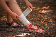 Woman applying compression bandage on her leg Royalty Free Stock Photos