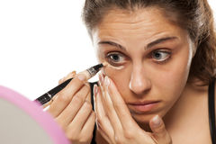 Woman applying concealer Stock Photos
