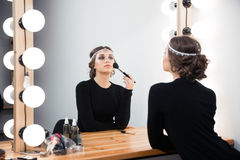 Woman applying cosmetic with brush Royalty Free Stock Photography