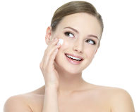 Woman applying cosmetic cream on face Stock Images