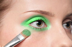 Woman applying cosmetic paint brush on eye zone Stock Photography