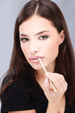 Woman applying cosmetic pencil Royalty Free Stock Photography