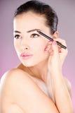 Woman applying cosmetic pencil on eye Stock Photos