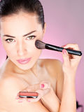 Woman applying cosmetic powder brush Royalty Free Stock Image