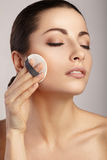 Woman applying cosmetic sponge on her face Stock Photos