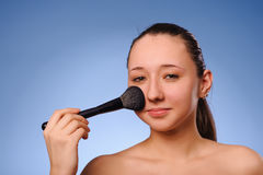Woman applying cosmetics Stock Image