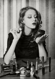 Woman applying cosmetics. On the table Royalty Free Stock Images