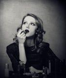 Woman applying cosmetics. Retro view Stock Photo