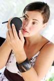 Woman applying cosmetics Stock Photo