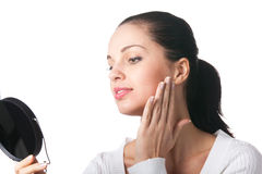 Woman applying cosmetics. With mirror, isolated royalty free stock images