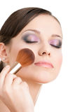 Woman applying cosmetics to her face Royalty Free Stock Photography
