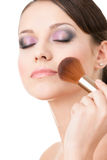 Woman applying cosmetics to her face Stock Photos