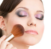 Woman applying cosmetics to her face Royalty Free Stock Photo