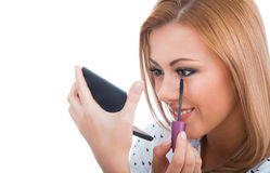 Woman applying cosmetics to her face Stock Image