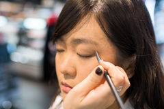 Woman applying cosmetics. Young Asian woman applying eye liner with a small brush Royalty Free Stock Photo