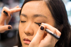 Woman applying cosmetics. Young Asian woman applying eye liner with a small brush Royalty Free Stock Images