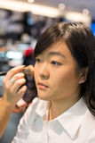 Woman applying cosmetics. Young Asian woman applying facial powder with a brush Stock Photo