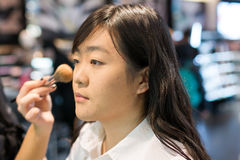 Woman applying cosmetics. Young Asian woman applying facial powder with a brush Royalty Free Stock Photo