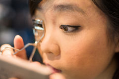 Woman applying cosmetics. Young Asian woman fixing her eye lash with clipper Royalty Free Stock Photography