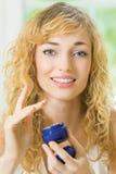 Woman applying cream royalty free stock photography