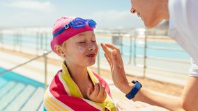 Girl getting skin care after swimming lessons. Woman applying cream on the cafe of girl wrapped in towel after swimming. Girl getting skin care after swimming stock photo