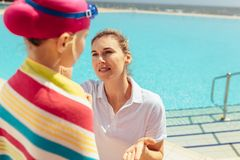 Mother taking care of girl after swimming lessons. Woman applying cream on the cafe of girl wrapped in towel after swimming lesson. Mother putting some cream on stock photo