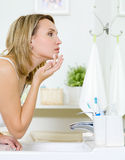 Woman applying  cream on face - indoors Royalty Free Stock Photo