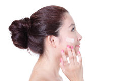 Woman applying cream on face in profile Stock Photography