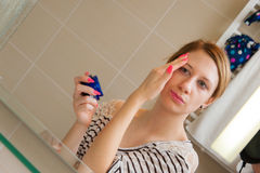 Woman Applying Cream on Face Stock Photos